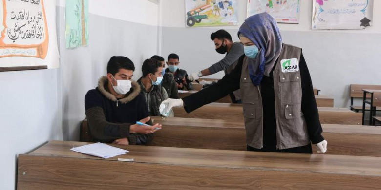 In cooperation with the Free University of Aleppo, student volunteers distribute medical masks and hand sanitizer to students sitting for exams. March 2021. Credits: Free University of Aleppo